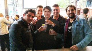 Four men posing with the cardboard cut out of Justin Trudeau in Austin
