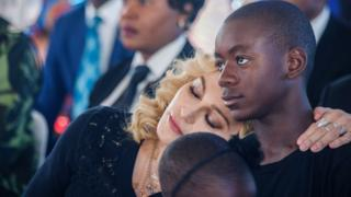 US pop star Madonna (left) rests her head on the shoulder of her adopted son David Banda during the opening ceremony of the Mercy James Children's Hospital at Queen Elizabeth Central Hospital in Blantyre, Malawi, on 11 July 2017.