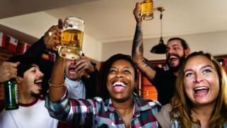 Men and women raise beer glasses