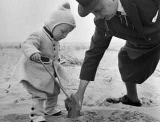 man helps child build sandcastle