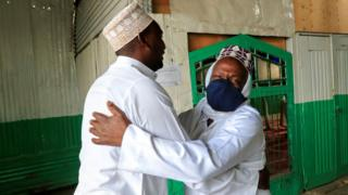 Muslim faithful embrace before performing the Eid al-Fitr prayers, marking the end of the holy fasting month of Ramadan, outside a mosque closed amid concerns about the spread of the coronavirus disease (COVID-19), in Nairobi, Kenya, May 24, 2020.
