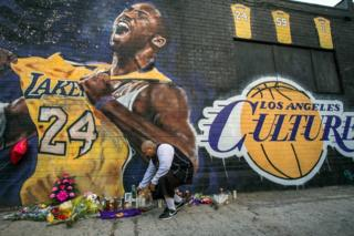 Flowers are laid next to a mural of the player in downtown Los Angeles.