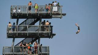 People line up to jump off a diving tower on the shore of the lake Ammersee near the small Bavarian village of Utting, southern Germany