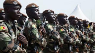 Malian soldiers stand holding rifles and listening to their national anthem during celebrations to mark the country's independence
