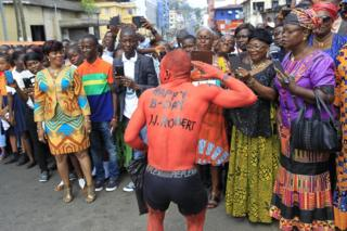 "B-Day J.J. Robert"" greeting painted on his body as he jons a parade in commemoration of the 208th birth anniversary of Liberia""s first (and sixth) President Joseph Jenkins Roberts in Monrovia, Liberia, 15 March 2017"