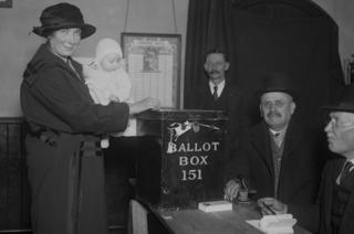 Mother posts vote in ballot box in South Dulwich while holding baby