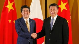 Japanese Prime Minister Shinzo Abe (R) shakes hands with Chinese President Xi Jinping