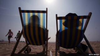 Sunbathers in their deckchairs on a beach