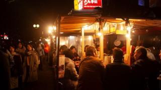 Khách hàng đang lướt qua các yatai nằm dọc bờ kênh quận Nakasu của thành phố Fukuoka