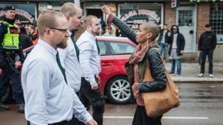 A lone woman stands with raised fist opposite the uniformed demonstrators in Sunday's Nazi demonstration in Borlange, Sweden