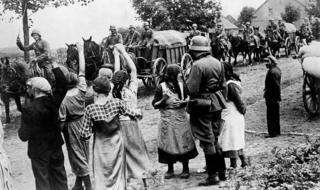 East Prussia. Dân thiểu số Đức tại Đông Phổ (East Prussia), nay là vùng Đông Bắc Ba Lan, chào đóng quân đội phát-xít. Trái với hình ảnh tuyên truyền của chế độ Nazi, đa số bộ binh Đức di chuyển bằng xe ngựa, và xe tăng chỉ để cho các lực lượng tiền phương.