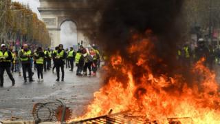 Протестувальники біля Тріумфальної арки в Парижі, поруч горять барикади