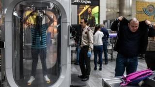 Pessoas passam por inspeção de segurança em aeroporto