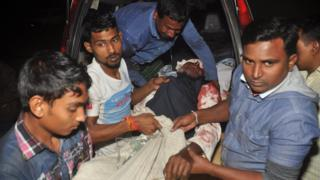 A man injured in an attack on a Shia mosque is carried for treatment in Bogra, Bangladesh