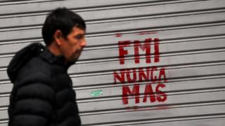 "Man walks past graffiti reading ""IMF never again"" in Buenos Aires, 1 June 2018"