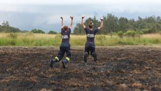 Firefighters in NSW jump in celebration of rain over fire grounds