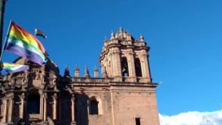 Vista de prédio histórico em Cusco com bandeiras de arco-íris que representam a cidade