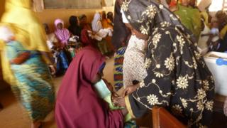 A health worker (R) vaccinates a child at a public health centre where children are being vaccinated against polio in Kano, northern Nigerian, on February 13, 2013.