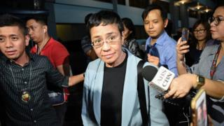 Philippine journalist Maria Ressa (C) is surrounded by the press as she is escorted by a National Bureau Investigation (NBI) agent (L) at the NBI headquarters after her arrest in Manila on February 13, 2019.