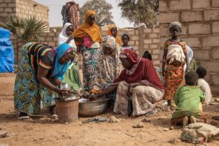Women and children stand outside accommodation made available by the community for Internally Displaced People (IDP) from northern Burkina Faso in Kaya, on 22 January 2019.