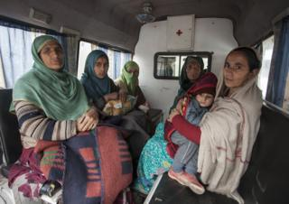 Women and children being evacuated in an ambulance.