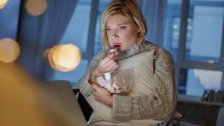 Mujer triste comiendo dulces frente a la computadora.