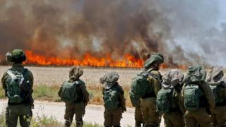 Israeli soldiers walk amidst smoke from a fire in a wheat field near the Kibbutz of Nahal Oz, along the border with the Gaza Strip, on May 14, 2018