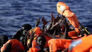 Migrants raise their hands to grab a life jacket on a boat off Libya's coast. Photo: 2 February 2017
