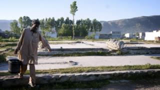 A man carrying a bucket of water makes his way across the razed compound