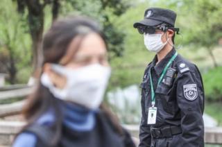 浙江的一个公园里,保安人员用AR(扩增虚拟实境)设备测量公园游客的体温。