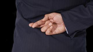 Man crossing fingers behind his back