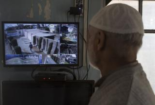 An elderly man watches the monitor of a CCTV cameras in his home