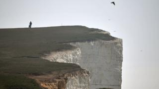 A person walks along Beachy Head, close to Eastbourne, on the south coast of England on Sunday.