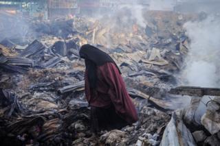 Eine Frau geht durch rauchende Trümmer