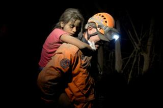 A rescue worker carries a child covered with ash
