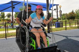 A visitor in a wheel chair swing