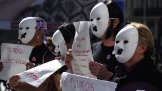 Masked demonstrators in Madrid hold posters against gender violence