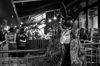 A man in a bunny mask smokes