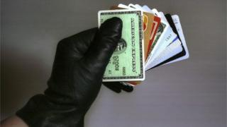 A gloved hand holding bank cards