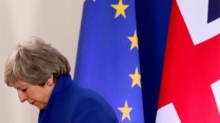 Тереза Мей поруч з прапорами ЄС та Британії