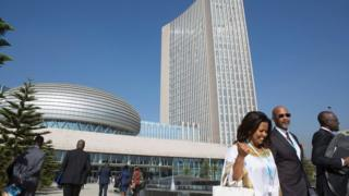 Delegates arriving to attend the 28th African Union (AU) Heads of State Summit are pictured against a background of the AU hearquarters prior to the opening ceremony on January 30, 2017 in Addis Ababa