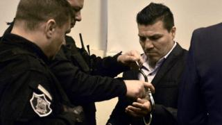 In this handout photo released by Telam, Argentine former boxer Carlos Baldomir (R) have his handcuffs removed at a court in Santa Fe, Argentina on July 31, 201