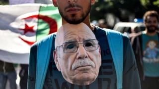 An Algerian protester hangs around his neck a mask representing Lakhdar Bouregaa, a well-known war veteran who was arrested by the authorities last summer, during an anti-government demonstration in the capital Algiers on November 1, 2019. - Demonstrators converged on Algiers in their thousands for a massive anti-government rally called to coincide with official celebrations of the anniversary of the war that won Algeria's independence from France.