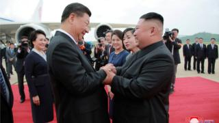 Xi Jinping and Kim Jong-un holding hands