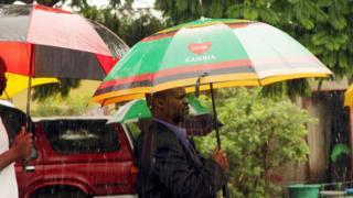 Zambia man dey hold umbrella under rain