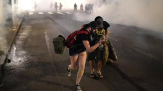 Two protesters flee through tear gas after federal officers dispersed a crowd of about a thousand at a courthouse in Portland, 21 July 2020