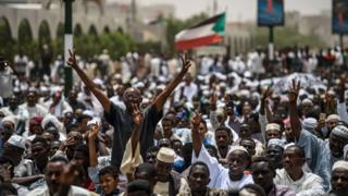 Sudanese protesters flash the victory sign ahead of a friday prayer outside the army headquarters in the capital Khartoum on April 19, 2019. -