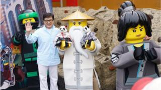 Jackie Chan poses with Ninjago Lego figures