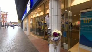 Flowers taped to a pillar in front of Halifax Bank