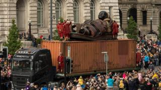 A huge puppet named Little Boy Giant is transported along the dockside